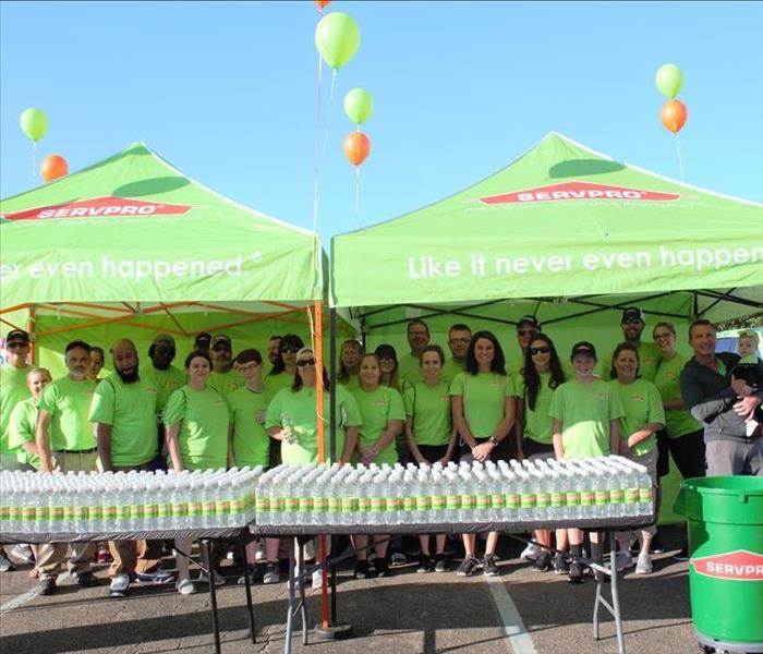 members of SERVPRO in SERVPRO green t-shirts, rows of water bottles sit on two tables under two green SERVPRO tents