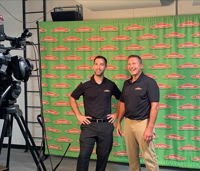 image of SERVPRO owners standing and smiling while on camera for the local news