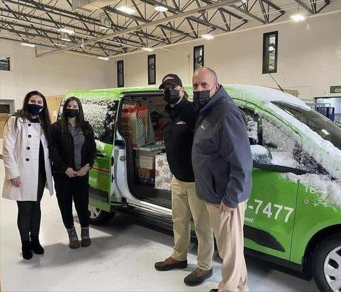 image of servpro employees next to a vehicle full of gifts to be donated to local charity