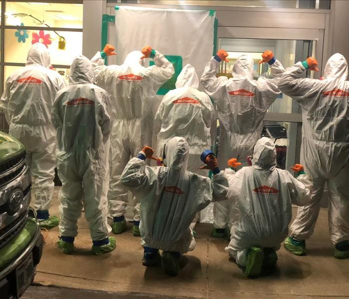 Backs of a group of SERVPRO employees in PPE after sanitizing a facility
