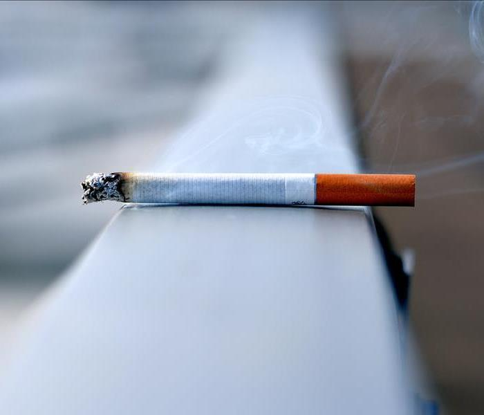 burning cigarette lying on a flat surface